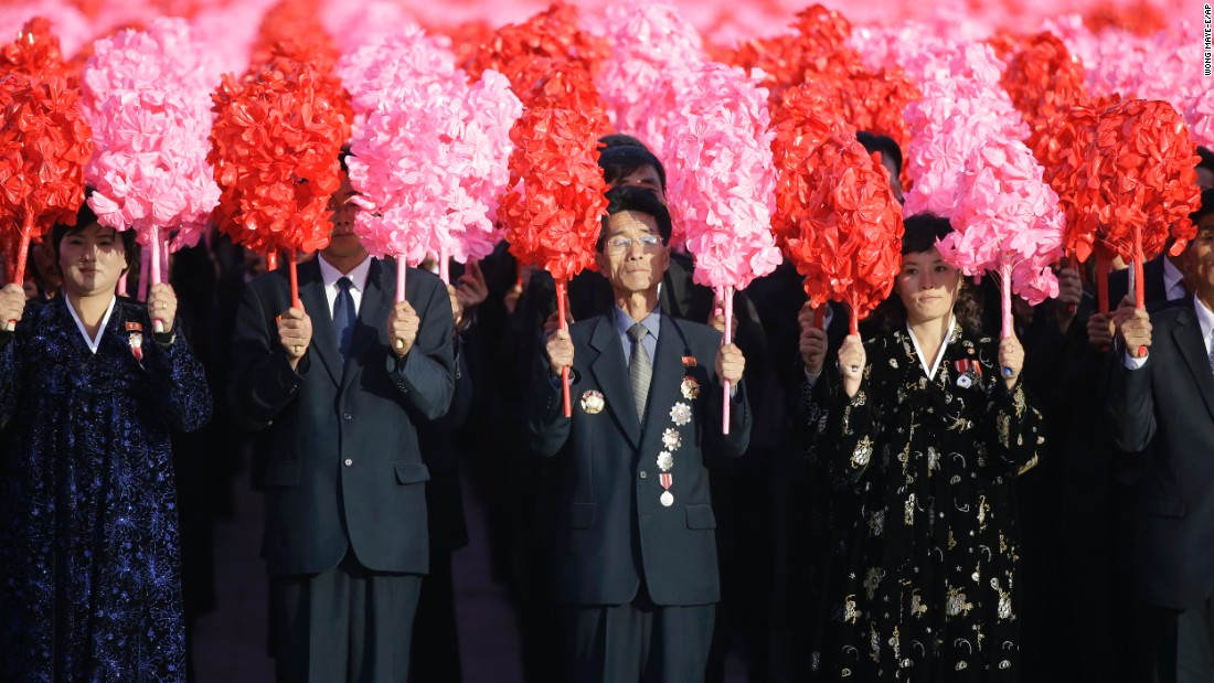 North Koreans hold decorative flowers during the parade.
