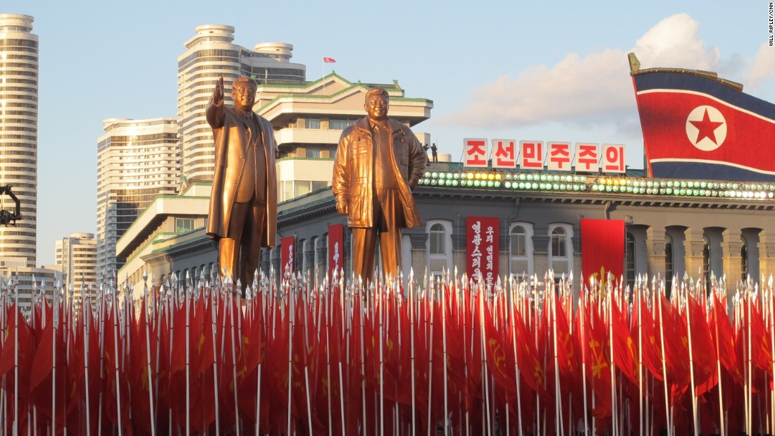 North Korean soldiers march below statues of North Korean founder Kim Il Sung and his son, Kim Jong Il.