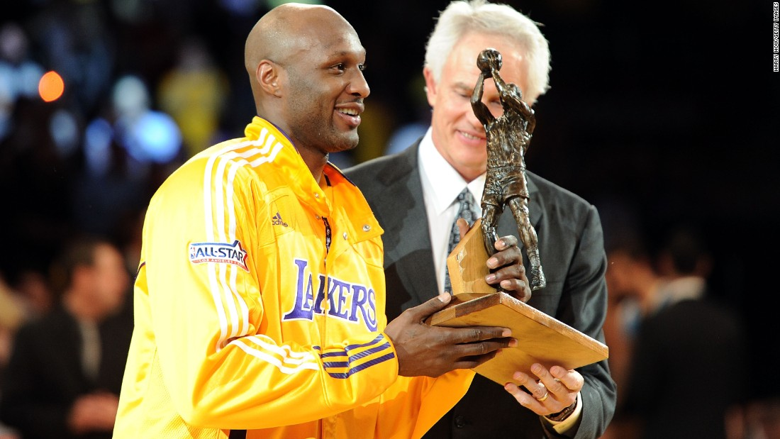 Odom receives the Sixth Man of the Year Award from Lakers general manager Mitch Kupchak in April 2011. The award honors the NBA's best player in a reserve role.