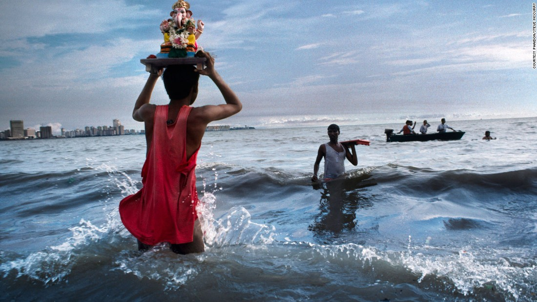 "This image depicts a devotee carrying a statue of Lord Ganesh into the waters of the Arabian Sea, during the immersion ritual off Chowpatty Beach in Mumbai, 1993<br /><br />""For all the silliness and vulgarity that McCurry photographs in modern urban India, he never forgets that India is still a profoundly sacred land,"" says Dalrymple.<br /><br />""It is, after all, a country with 2.5 million places of worship, but only 1.5 million schools and barely 75,000 hospitals. Pilgrimages account for more than half of all package tours, and the bigger pilgrimage sites vie with the Taj Mahal in popularity: 17.25 million trekked to the shrine of Vaishno Devi."""