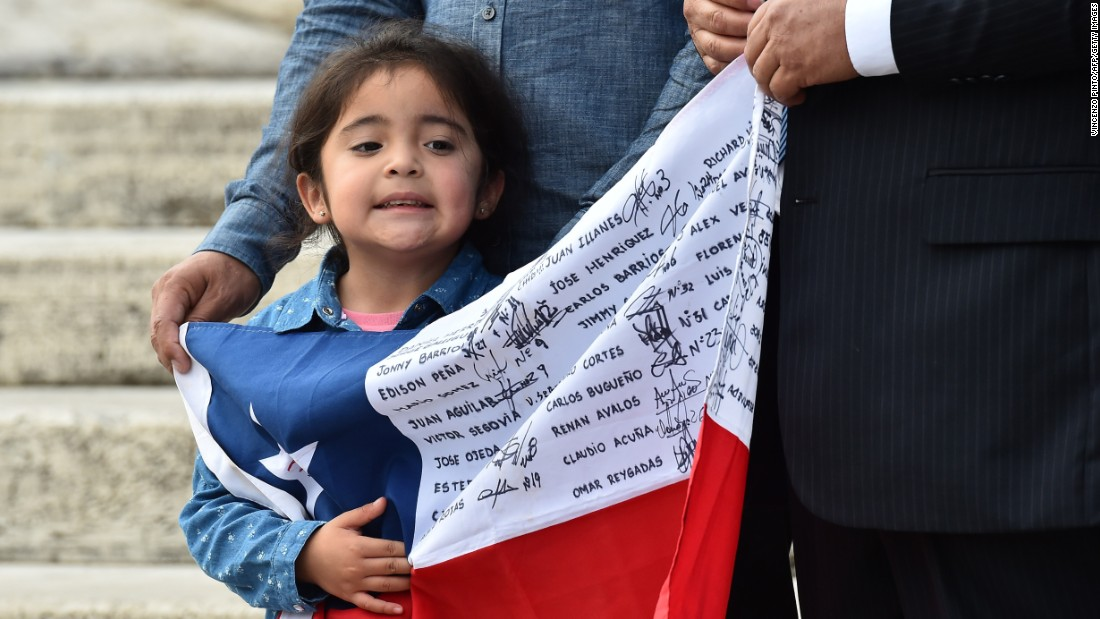 A little girl waiting for Pope Francis holds a Chilean national flag with the names of rescued miners. The men gave the Pope a signed helmet and an enlarged framed message.