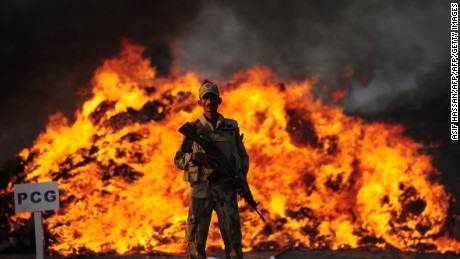 A Pakistani soldier of the Anti Narcotics Force stands beside a burning pile of seized drugs on the outskirts of Karachi on October 15, 2015. Pakistani authorities torched tonnes of seized drugs, including heroin, hashish, cocaine, and opium at a ceremony attended by government and anti-narcotics officials. AFP PHOTO/ ASIF HASSAN        (Photo credit should read ASIF HASSAN/AFP/Getty Images)