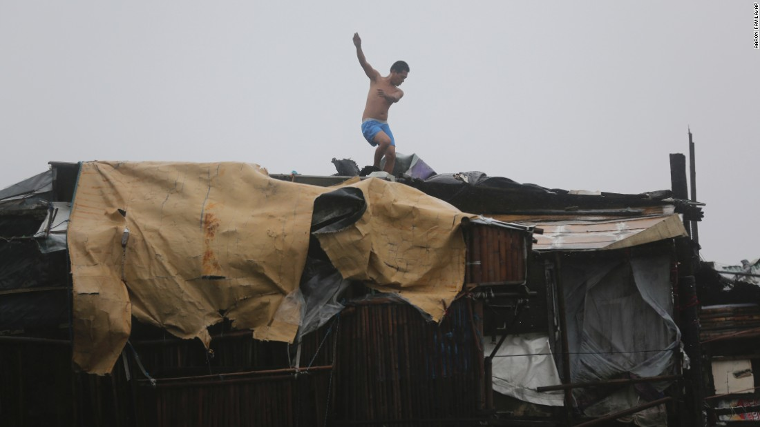 A man is thrown off balance by strong winds while he tries to reinforce the roof of his house on October 18 in Navotas.