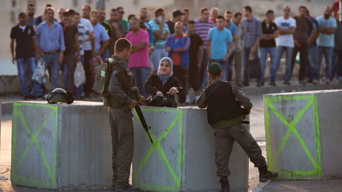 Israeli border police check  Palestinians' identification on October 18 at a checkpoint as they exit the Arab neighborhood of Issawiyeh in Jerusalem.