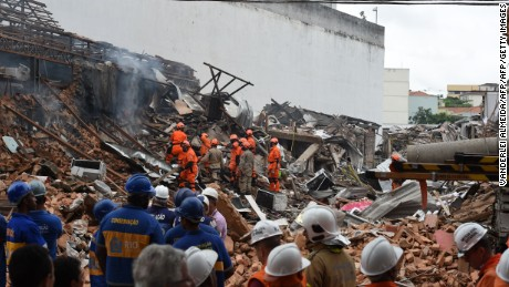 Firefighter rescue teams search for victims after an explosion swept two restaurants and a pharmacy in a suburban neighbourhood of Rio de Janeiro, on October 19, 2015. A powerful explosion suspected to be caused by illegally stockpiled gas canisters ripped through a Rio de Janeiro neighbourhood Monday, injuring at least seven people and destroying homes and businesses. Footage on Globo television from the Sao Cristovao area of northern Rio, in a neighborhood near the giant Maracana stadium, showed firefighters dousing flames and clawing through piles of twisted metal and rubble searching for survivors.  AFP PHOTO / VANDERLEI ALMEIDA        (Photo credit should read VANDERLEI ALMEIDA/AFP/Getty Images)