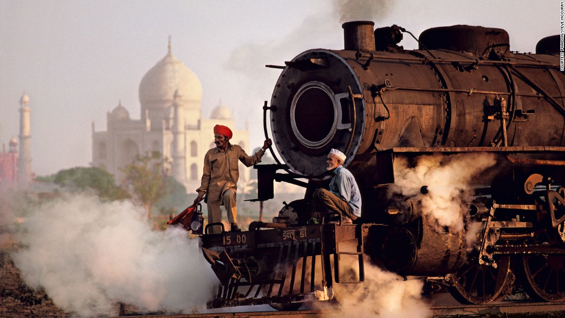 "The gleaming white marble of the Taj Mahal is vividly contrasted against the dirty black steam of a passing train, in this 1983 photograph. <br /><br />Scottish historian and writer of numerous books on India, William Dalrymple, sees  McCurry as a master at capturing India's ""extraordinary contradictions.""<br /><br />""Perhaps most stark among the extremes McCurry illustrates are those between India's rich and poor,"" says Dalrymple in his written introduction to ""India.""<br /><br />""We see the landowner with his hunting trophies pinned to the wall, and we see the beggar children dying beside the railway tracks, invisible to the passengers on the train; we see the soaked beggar children fingering desperately at the windows of the taxi; and we see the Bombay elite, coiffed and laundered, with their fleets of vintage cars and uniformed chauffeurs..."""