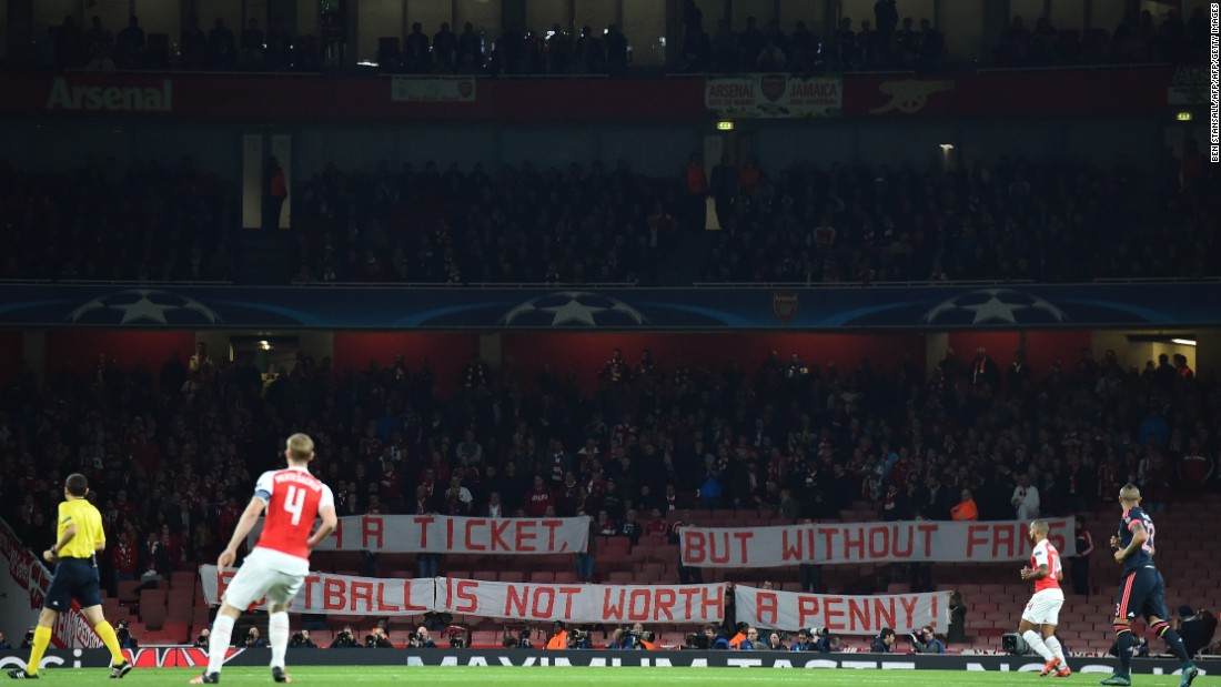 Bayern Munich fans hold a banner as they protest in the stands against the cost of tickets, at the beginning of the UEFA Champions League football match between Arsenal and Bayern Munich at the Emirates Stadium in London.