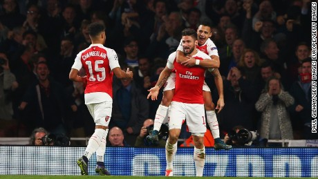 Olivier Giroud of Arsenal (C) celebrates with Alex Oxlade-Chamberlain (15) and Alexis Sanchez as he scores their first goal during the UEFA Champions League Group F match between Arsenal FC and FC Bayern Munchen at Emirates Stadium on October 20, 2015.