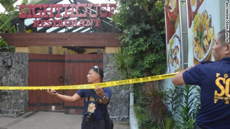 Police mark the crime scene with yellow tape where two Chinese diplomats were killed in Cebu, Philippines on Wednesday.