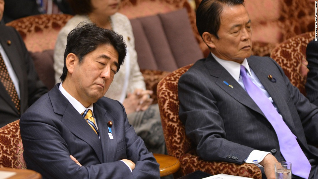 "Japanese Prime Minister Shinzo Abe (L) and Finance Minister Taro Aso ""listen"" to a question from an opposition lawmaker during a budget session at the National Diet in Tokyo in February 2013."