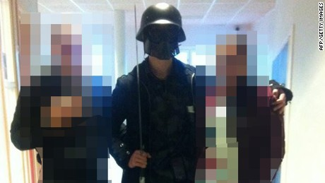 This picture, made available to AFP by a student, shows a masked man armed with a sword posing for a photo with two other students before attacking students and staff at the primary and middle school in Trollhattan, Sweden on October 22, 2015.
