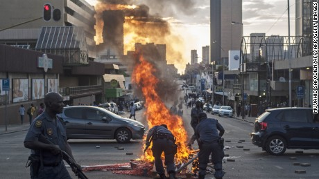 "Police officers attempt to put-out a street fire during clashes between students and police in front of the Union Building on October 23, 2015 in Pretoria. South African police on October 23 fired rubber bullets and tear gas at students protesting outside government headquarters over hikes to university fees that President Jacob Zuma was forced to scrap after days of unrest. Zuma had been due to address the volatile crowd of thousands after talks with student leaders and university officials inside the buildings, but instead he read a short statement at a televised press briefing. ""We agreed that there will be a zero increase of university fees in 2016,"" he said. AFP PHOTO/MUJAHID SAFODIENMUJAHID SAFODIEN/AFP/Getty Images"