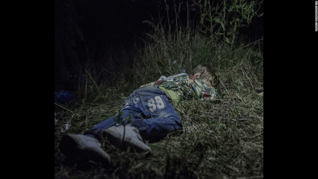 "Ahmed, 6, sleeps on the ground in Horgos, Serbia. The adults were still sitting around after midnight, formulating plans for how they were going to get out of Hungary without registering themselves with the authorities. Ahmed carries his own bag over the long stretches that his family walks by foot. ""He is brave and only cries sometimes in the evenings,"" says his uncle, who has taken care of him since his father was killed in their hometown in northern Syria."
