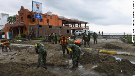 Mexican soldiers remove sand from the street in Manzanillo, state of Colima, after Hurricane Patricia hit the shore of neighbouring Jalisco state, on October 24, 2015. Record-breaking Hurricane Patricia weakened to a tropical storm over north-central Mexico on Saturday, dumping heavy rain that triggered flooding and landslides but so far causing less damage than feared.   AFP PHOTO/OMAR TORRES        (Photo credit should read OMAR TORRES/AFP/Getty Images)