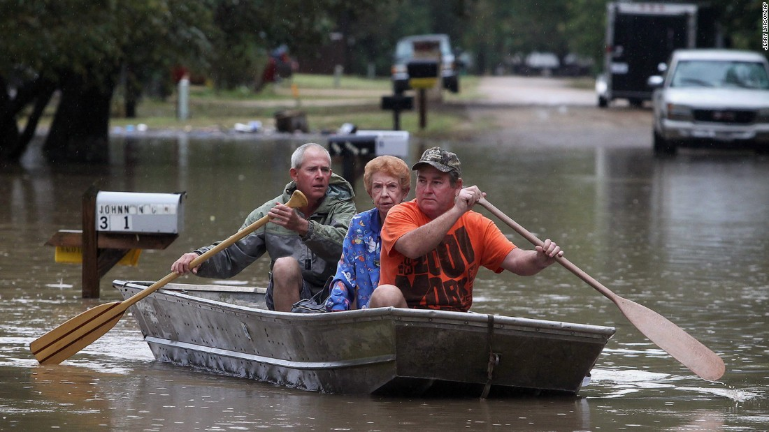 J.B. Neckar, right, and his brother Johnny Neckar paddle their mother Gelene Neckar from her flooded home near Downsville, Texas, on October 24. Heavy rains have forced parts of the Brazos River out of its banks and are endangering homes in the small community just outside of Waco.