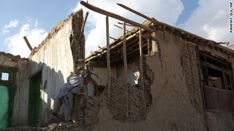 A boy looks at a damaged house in Kabul, Afghanistan.