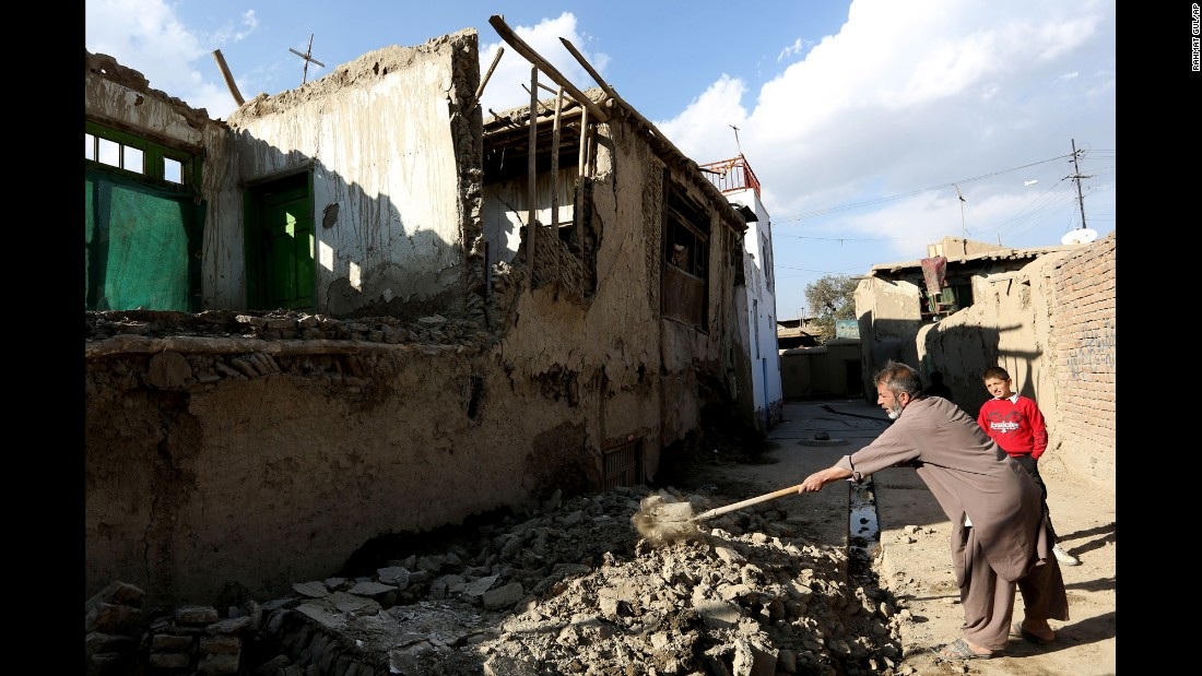 A man clears rubble from a damaged house in Kabul, Afghanistan.