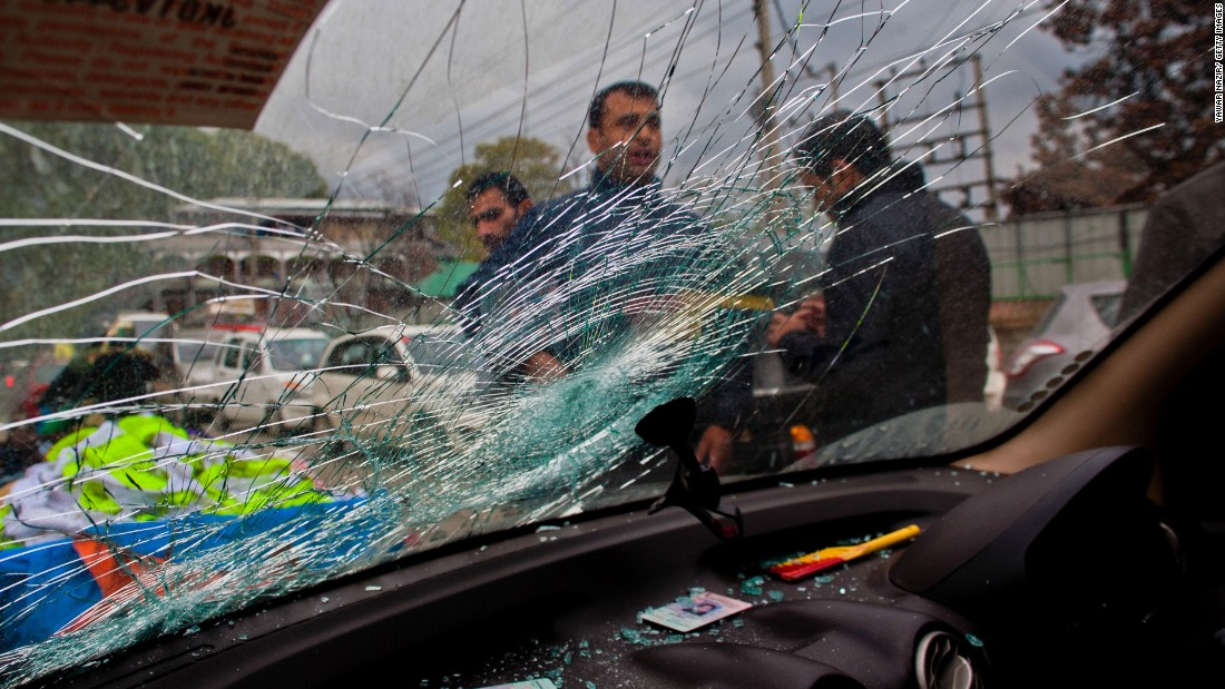 People stand next to a car damaged by a tree branch in Srinagar, India.