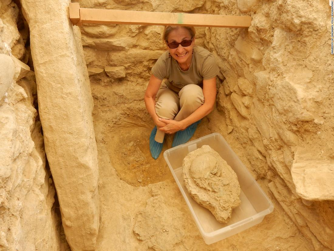 "Sharon Stocker with the 3,500 year-old skull found in the warrior-king's tomb. ""We have no idea of the identity of this man,"" she said, other than he was important and rich. ""We are looking at a period in Greece where people where usually buried with ceramic objects but this man was so rich that there were no ceramics. He was buried with bronze, silver and gold."""