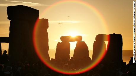People watch the midsummer sun as it rises over Stonehenge on June 21, 2005, on Salisbury Plain, England.