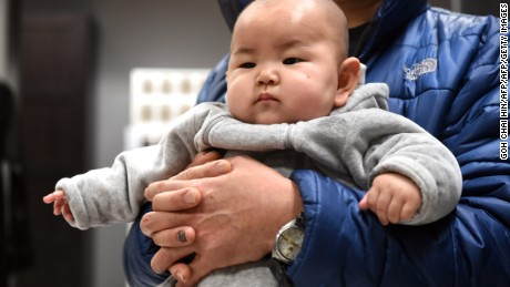 This picture taken on January 19, 2015 shows a Chinese baby in the arms of his father at a furniture store in Beijing.  China's working-age population continued to fall in 2014, the government said on January 20, as Beijing struggles to address a spiralling demographic challenge made worse by its one-child policy.    AFP PHOTO/GOH CHAI HIN        (Photo credit should read GOH CHAI HIN/AFP/Getty Images)