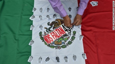 A man holds portraits of the missing students to a Mexican flag during a protest in Mexico city, on September 26, 2015, to commemorate the first anniversary of Ayotzinapa students  disappearance. The students, from a rural teachers college in the southern state of Guerrero, disappeared after they were attacked by local police in the city of Iguala on September 26, 2014.  AFP PHOTO/YURI CORTEZ        (Photo credit should read YURI CORTEZ/AFP/Getty Images)