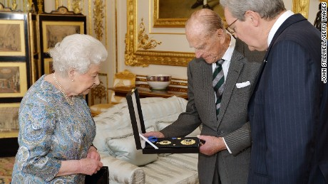 Britain's Queen Elizabeth II (L) presents Britain's Prince Philip, Duke of Edinburgh (C) with the Insignia of a Knight of the Order of Australia as Australian High Commissioner Alexander Downer (R) looks on in the white drawing room at Windsor Castle, west of London, on April 22, 2015.  Queen Elizabeth II presented her husband Prince Philip with an insignia of his Australian knighthood, the awarding of which plunged Prime Minister Tony Abbott into crisis earlier this year.
