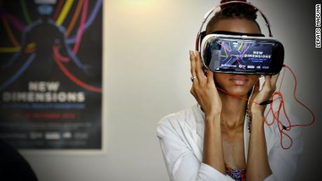 A woman tries a virtual reality headset at an exhibition at the African Futures Exhibition at the Goethe Insitut, Johannesburg.