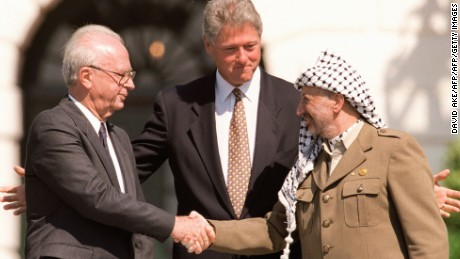 WASHINGTON, DC - SEPTEMBER 13:  US President Bill Clinton (C) stands between PLO leader Yasser Arafat (R) and Israeli Prime Minister Yitzahk Rabin (L) as they shake hands 13 September 1993 at the White House in Washington DC. Rabin and Arafat shook hands for the first time after Israel and the PLO signed a historic agreement on Palestinian autonomy in the occupied territories. Rabin was assassinated reportedly by a Jewish extremist 04 November 1995 after attending a peace rally in Tel Aviv.  (Photo credit should read J. DAVID AKE/AFP/Getty Images)