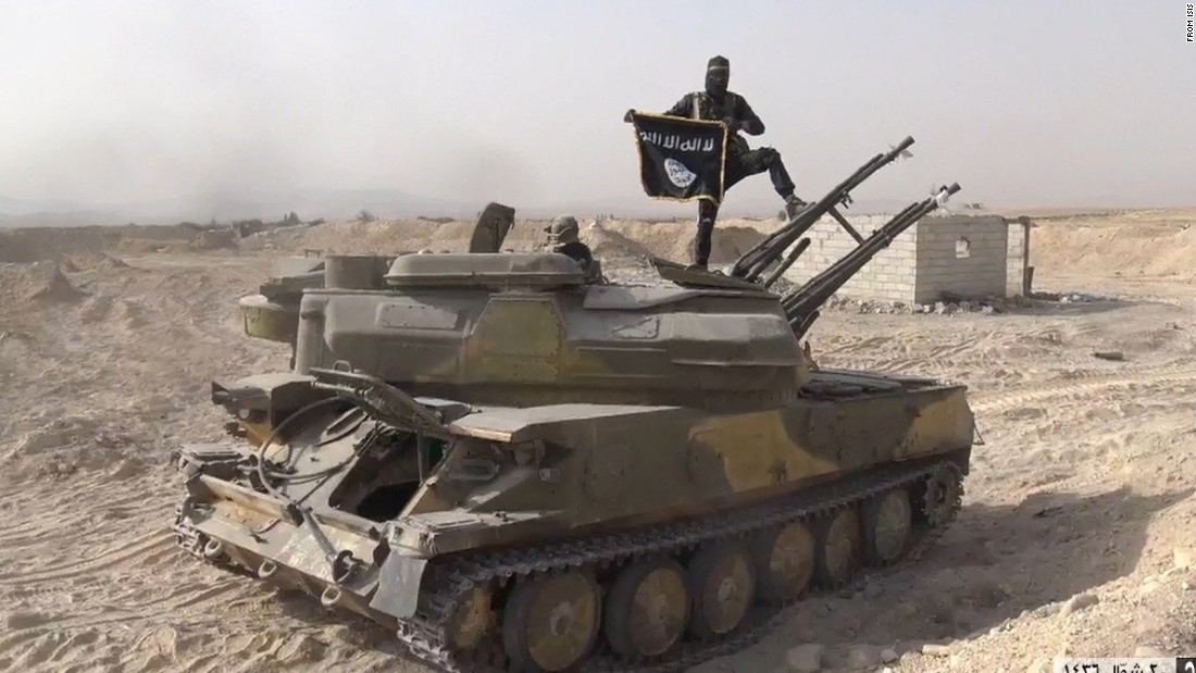 In this image taken from social media, an ISIS fighter holds the group's flag as he stands on a tank, purportedly captured when they took over the town of Qaryatain, Syria. ISIS, along with Boko Haram, is one of two groups accounting for 51% of claimed terrorism deaths in 2014.