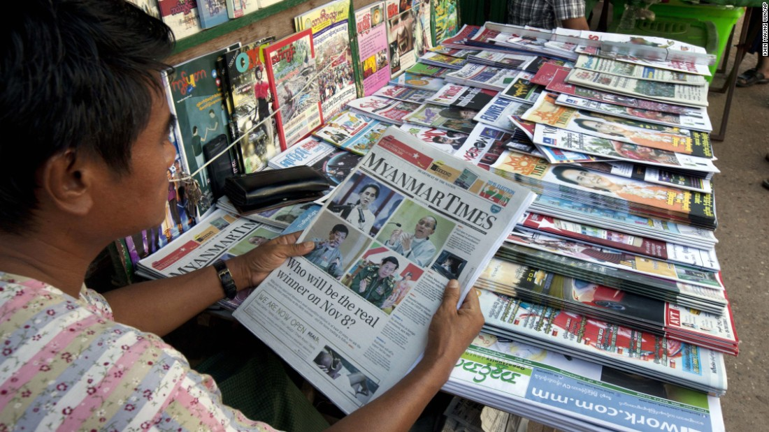 A vendor reads a local weekly journal showing a portrait of Myanmar opposition leader Aung San Suu Kyi, President Thein Sein and others.