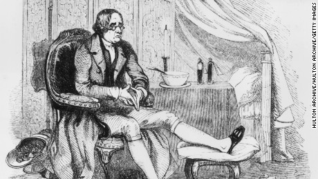 Circa 1800, a  man rests his foot, with his slipper slit to accommodate a foot swollen from gout.