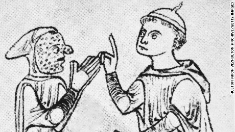 Circa 1200, a leper covered in sores approaches a man, making a gesture of supplication.