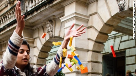 A woman throws Lego bricks into a BMW 5 series car, used as a receptacle for donations of Lego bricks in the courtyard of the Royal Academy in central London on October 30, 2015. The collection has been organised by Chinese artist and activist Ai Weiwei who, after having his official request for Lego bricks refused by the manufacturer, has called on the public to donate their bricks as part of his next project. AFP PHOTO / LEON NEAL        (Photo credit should read LEON NEAL/AFP/Getty Images)