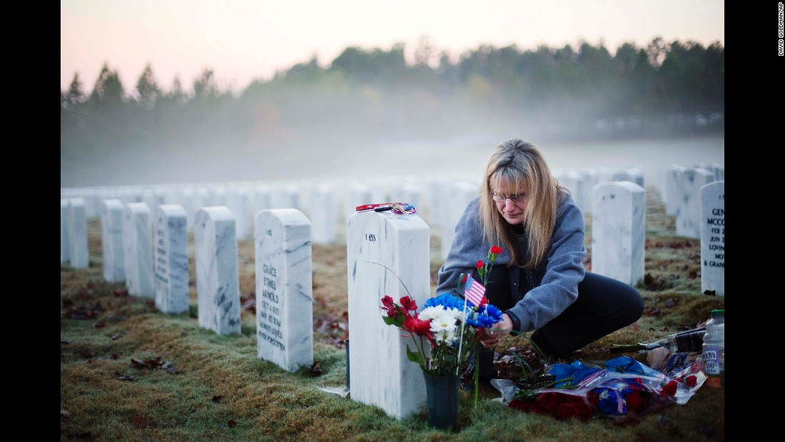 "Jiffy Helton Sarver places flowers at the grave of her son, Air Force 1st Lt. Joseph Helton Jr., at the Georgia National Cemetery in Canton, Georgia. He was killed while serving in Iraq in 2009. ""This was his favorite time of day,"" his mother said. ""He loved sunrises."""