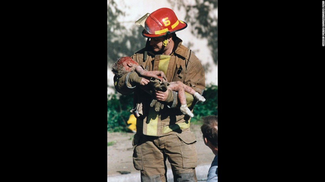 Oklahoma City firefighter Chris Fields holds Baylee Almon, an infant who was thrown from   a day care center inside the Alfred P. Murrah Federal Building when it was attacked on April 19, 1995. A truck loaded with explosives parked outside the building ignited, killing 168 people, including Baylee. The day before the bombing, she had celebrated her 1st birthday. Charles Porter IV heard the blast from a nearby bank where he worked, rushed to his car and took his Canon camera out of the trunk, said Buell. Porter made the picture just moments later.  He shot it with Kodak color negative film. His camera was equipped with a 70mm to 200mm zoom lens. Exposure details are unknown. Porter won the Pulitzer Prize in 1996.
