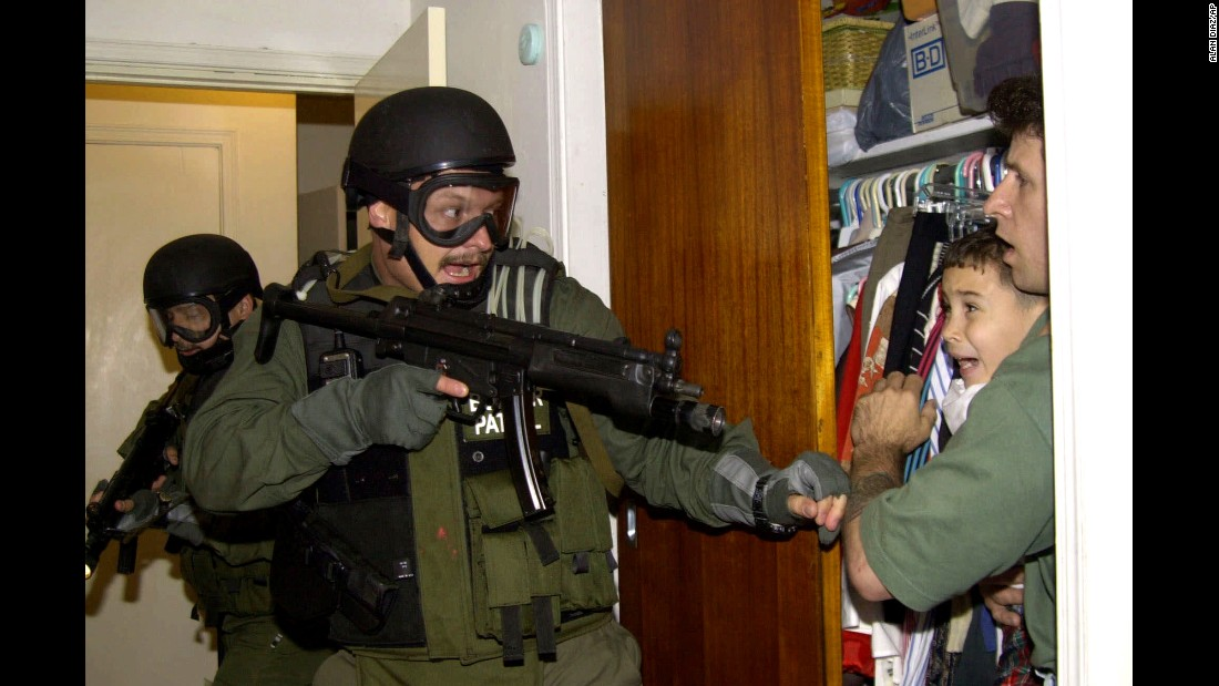 "U.S federal agents burst through the door of a Miami home on April 22, 2000, as they seized a <a href=""http://www.cnn.com/2015/10/14/world/elian-gonzalez-cuba-rewind/"" target=""_blank"">Cuban boy named Elian Gonzalez</a>. Elian was hiding in a closet with Donato Dalrymple, one of two men who had rescued him from a raft off the Florida coast months earlier. Elian's U.S.-based relatives lost a bitter legal battle with U.S. officials to prevent Elian from being returned to his father in Cuba. The Gonzalez family allowed photographer Alan Diaz to wait for the raid with Dalrymple and the boy. Diaz used a Nikon D1 digital camera with electronic flash and a 28-105/2.8 lens. The exposure was 250/5.6 and the lens was at 28mm most of the time."