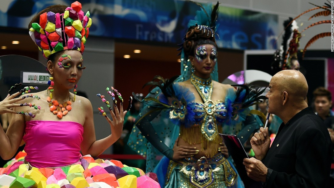 Gan says Malaysians are becoming more concerned with design. Here a judge looks at models as they present creations by stylists during a hairstyling and make-up competition in Kuala Lumpur.