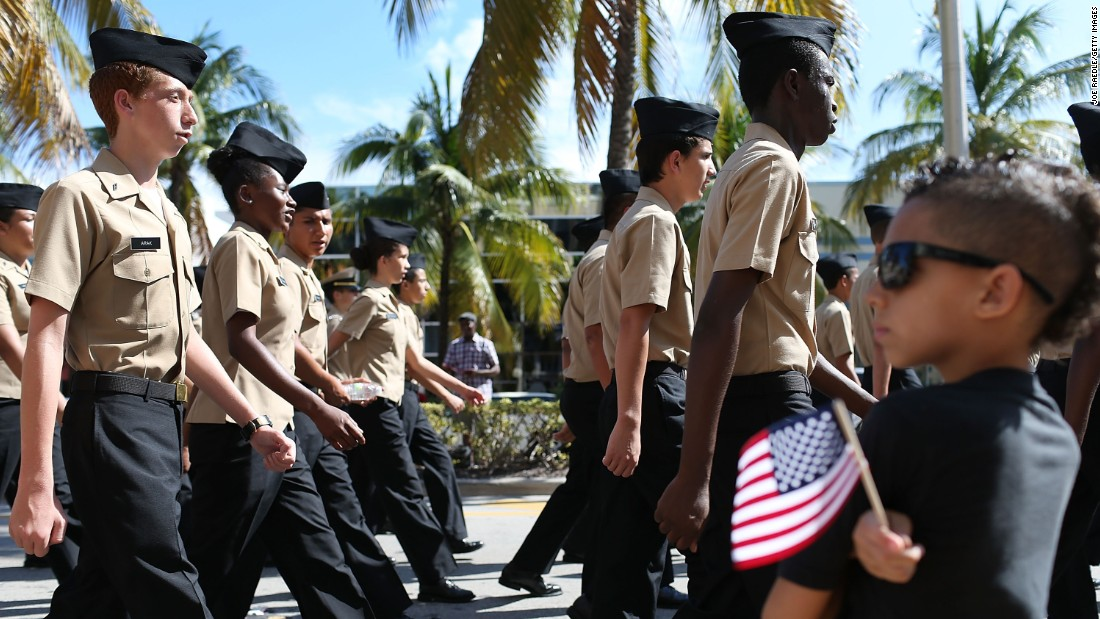 High school students in the Navy Junior ROTC program march past Xavier Barnett, front right, during a parade in Miami Beach, Florida.