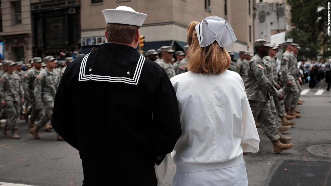 Two people dressed in classic uniforms watch the Veterans Day parade in New York City.
