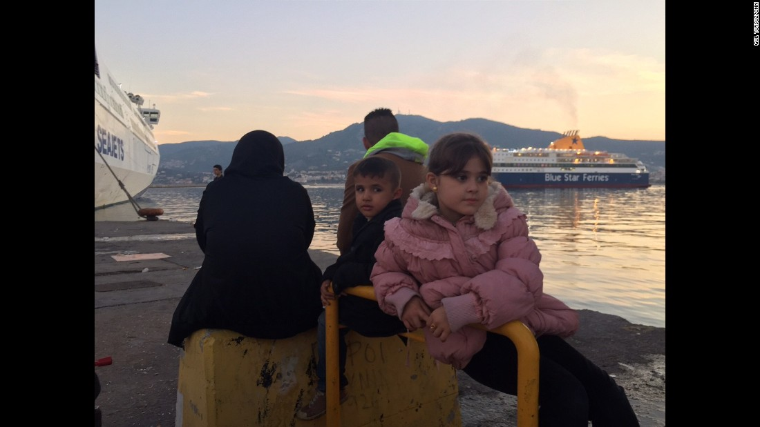 "Farah (R), 10, is from Baghdad. She has been waiting with her younger brother and parents for a boat to Athens for two days. When asked why they are leaving, she says, ""the situation in Baghdad is not good, that's what daddy said."""