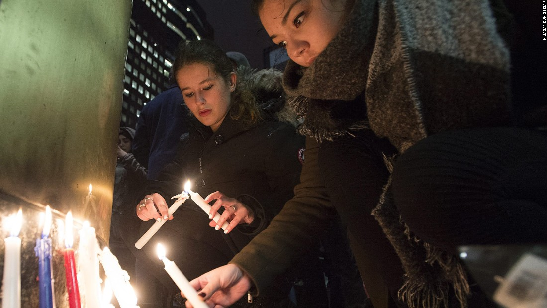 People light candles at a vigil outside the French Consulate in Montreal on November 13.