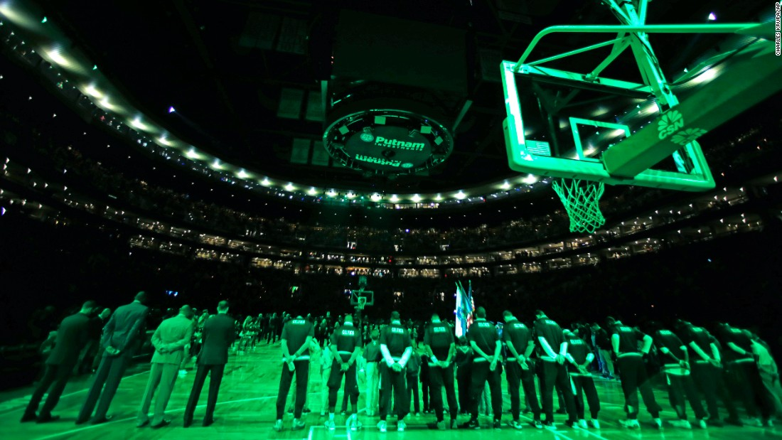 The house lights are shut off and scoreboard dark as Boston Celtics players pause for a moment of silence for the Paris victims before an NBA basketball game against the Atlanta Hawks in Boston on November 13.
