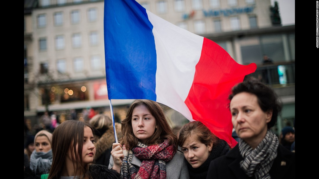 A woman holds a French flag during a gathering  in Stockholm, Sweden, on November 14.