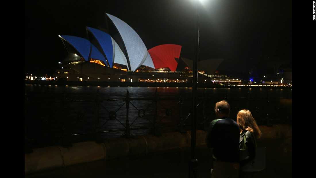 A couple surveys the signature sails of the Sydney Opera House lit in the colors of the French flag in Sydney on November 14.