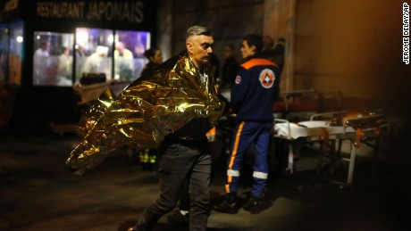 A victim walks outside the Bataclan theater in Paris, Friday Nov. 13, 2015. Well over 100 people were killed  in a series of shooting and explosions explosions. French President Francois Hollande declared a state of emergency and announced that he was closing the country's borders. (AP Photo/Jerome Delay)