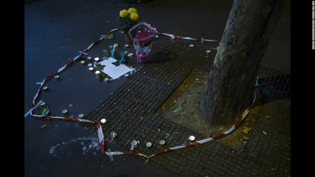 Candles and flowers are seen on November 14 at the spot where a victim died on the Rue de la Fontaine au Roi. Five people were killed in a shooting outside a bar in Paris' 11th district, according to prosecutor Francois Molins.