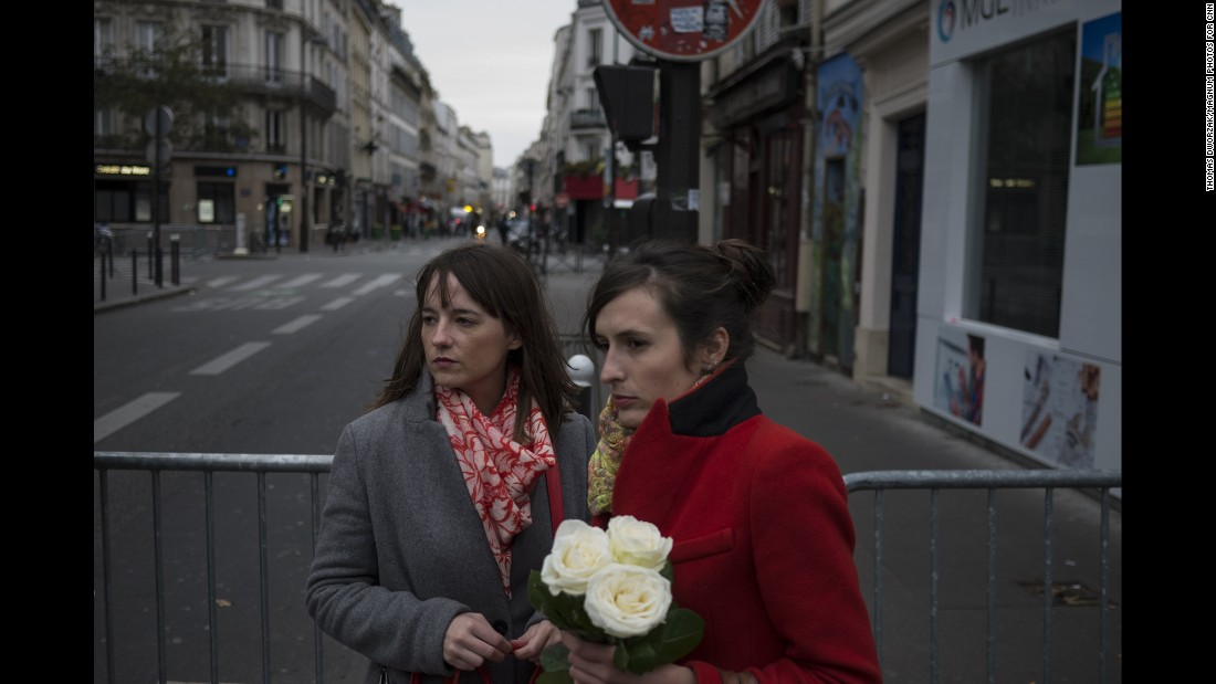 Women pay their respects near the Bataclan on November 14. Three gunmen shot concertgoers and held hostages late Friday night until police raided the building.
