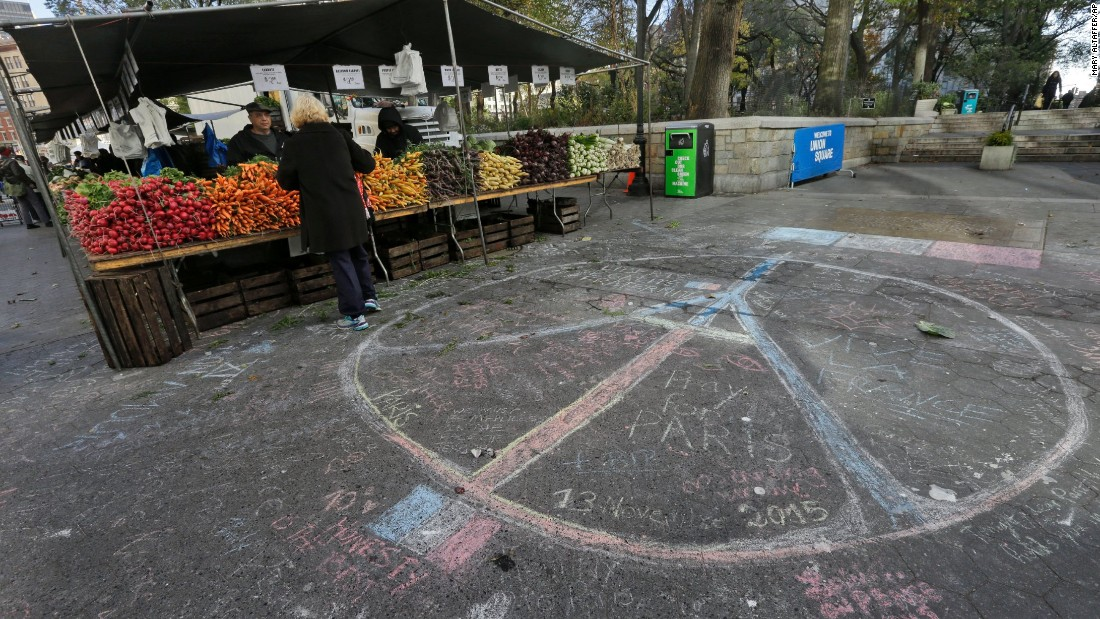 A woman shops for produce next to a peace sign drawn in solidarity to the people of Paris in New York's Union Square on Saturday, a day after the attacks.