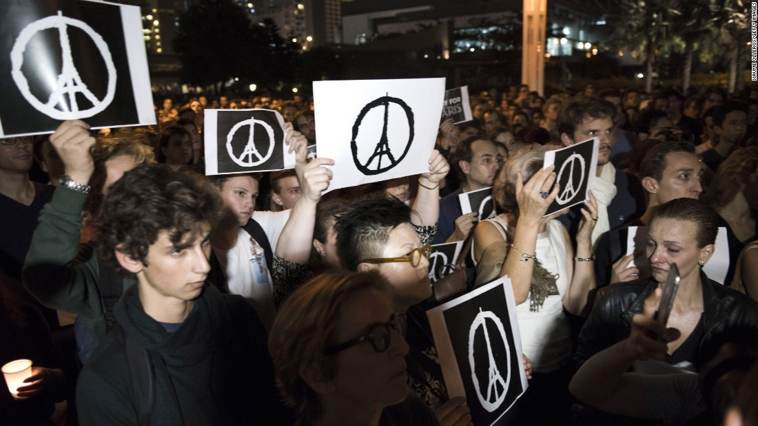 People hold peace signs as they gather during a memorial event in Hong Kong on November 14, 2015 for victims of the Paris terror attacks.